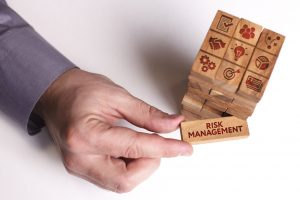 A businessman pulls out risk management piece from stack